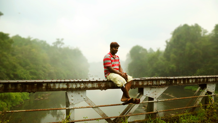 KODAIKANAL, INDIA - JUNE 29TH, 2015: A man siting on the bridge top with sea and sky background.