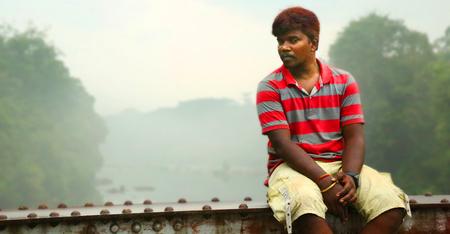 KODAIKANAL, INDIA - JUNE 29TH, 2015: A man siting on the bridge top