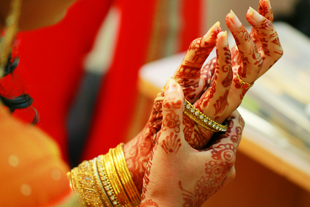 Indian bride putting on bangles closeup shot. Stock Photo