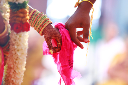 groom holds bride hand in south Indian traditional wedding Stock Photo