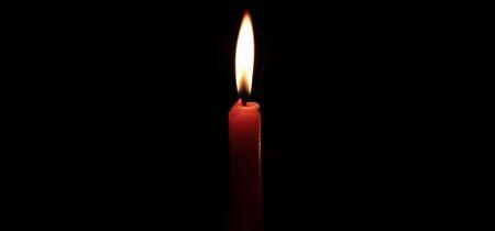 Vela encendida brillando intensamente en los fondos negros Foto de archivo