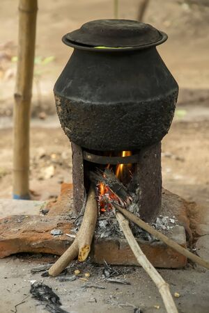 Old cooking pot stove using firewood.Large metal cauldron over a fire in a outdoor kitchen