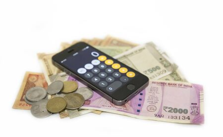 Close up view of Mobile Phone Calculate and new Indian rupees and coins