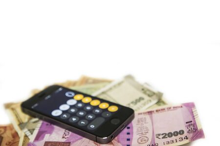 Mobile Phone and new Indian rupees banknotes on white background