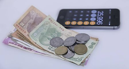 Mobile Phone Calculate and new Indian rupees blur background.
