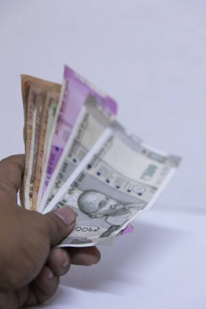 Hand holding Indian rupee notes against white background