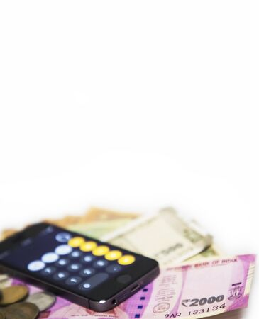 Finance concept - Mobile Phone Calculate and new Indian rupees blur on white background