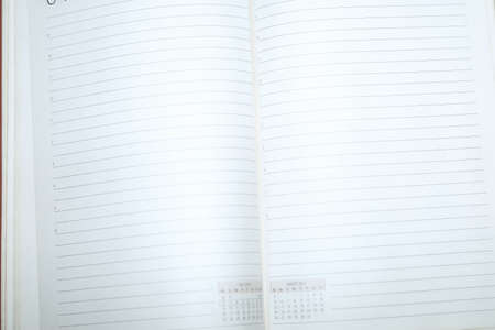 Blank diary sheet with rows on white background, close-up shot with selective focus.