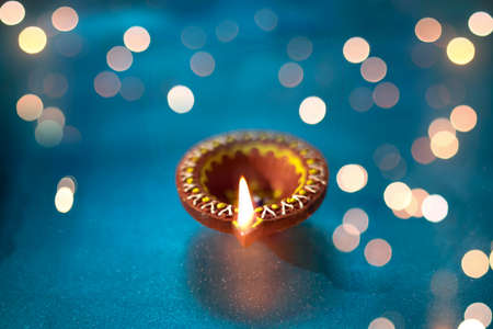 Diya lamps on a reflective base with glittering bokeh background
