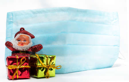 Merry Christmas Santa Claus with gift boxes and blue mask to protect against corona virus Imagens