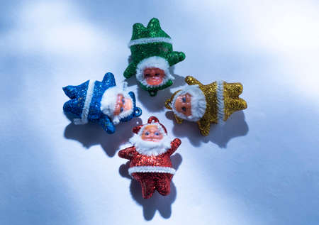 Multi-colored Santa Claus with sunlight rays on a white or snow background.