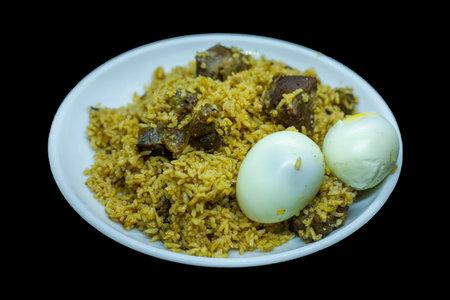 mutton biriyani with egg served in a serving white plate on black backgrounds Reklamní fotografie