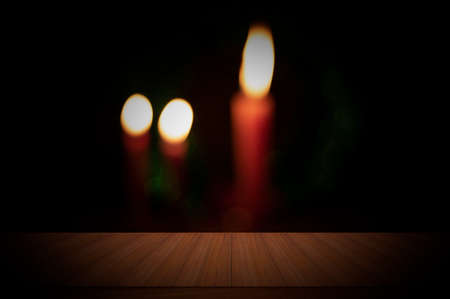 Wooden table with light backgrounds of dim three burning candles