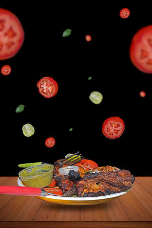 Homemade spicy food tandoori chicken with tomatoes, lemon and spicy flying on a dark backgrounds