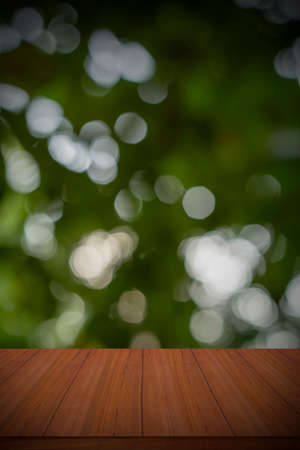 Abstract blurred green bokeh and brown wooden table backgrounds.