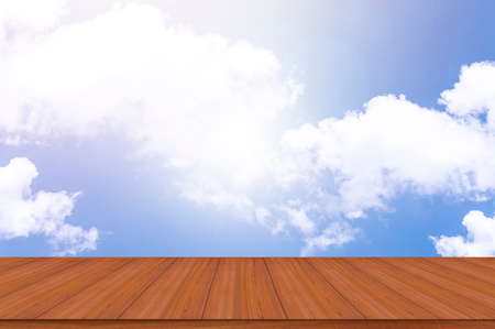 Empty wooden table top against a blue sky with sunlight backgrounds Standard-Bild