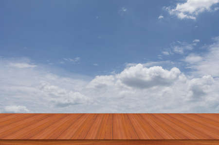 Brown wooden floor with perspective and cloudy sky background