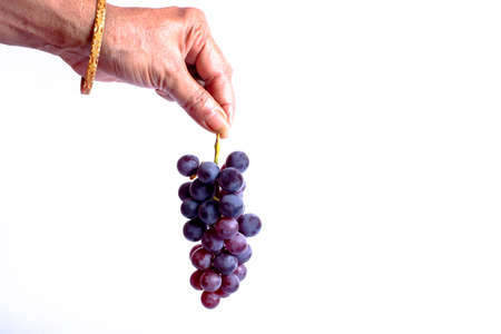 Female hand holding a bunch of fresh grape