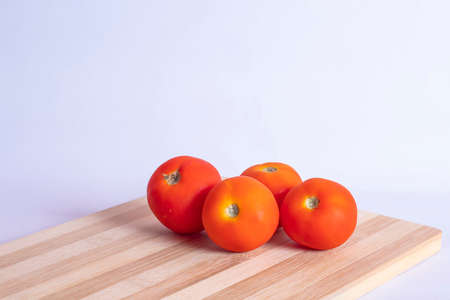 Fresh tomatoes on the kitchen cutting board isolated on white backgrounds.