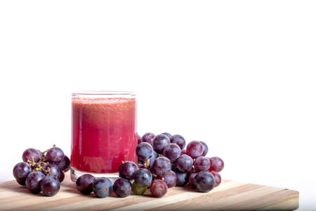 Grape juice in a glass on the table against a white backgrounds