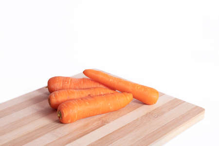 Carrots on on the cutting board against a white backgrounds