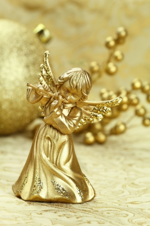 Christmas angel playing a flute with golden decoration at the background