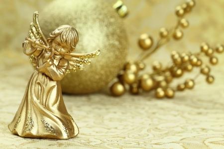 angel figurine: Christmas angel playing a flute with golden decoration at the background