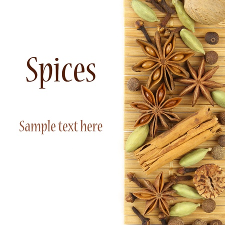 samples: Various spices - star anise, cinnamon, cardamom, all-spice, nutmeg and cloves - on a bamboo mat, isolated on white. With sample text  Stock Photo