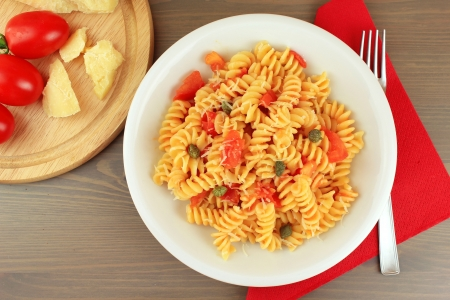 caloric: Dish of Italian pasta fusilli with fresh tomato sauce, capers and parmesan cheese