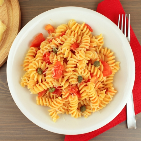 Dish of Italian pasta fusilli with fresh tomato sauce, capers and parmesan cheese