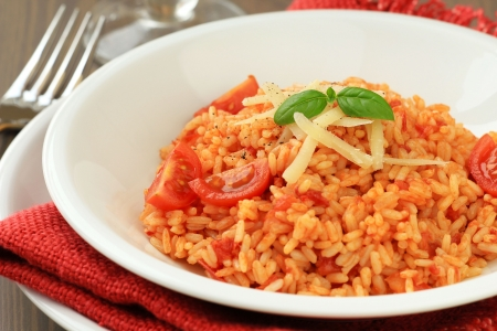 risotto: Italian risotto with tomatoes - Risotto al pomodoro - decorated with a fresh leaf of basil and parmesan cheese  Stock Photo