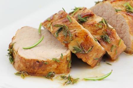 glazed: Glazed pork fillet on a white plate. Sliced pork tenderloin or sirloin in herbs and honey glaze