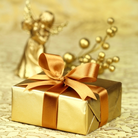 Christmas gift wrapped in a golden paper with a decorative bow and an angel at the background