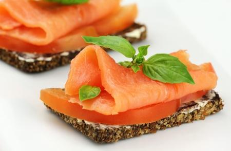 salmon ahumado: Delicioso canapé con salmón ahumado, tomates y albahaca fresca Foto de archivo