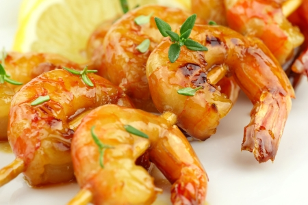 prawn skewers: Glazed shrimp skewers with thyme on white plate