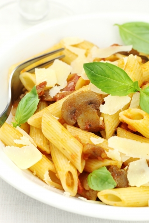 short pasta: Delicious Italian penne pasta with mushroom sauce, fresh basil and grated parmesan cheese