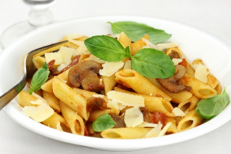 Delicious Italian penne pasta with mushroom sauce, fresh basil and grated parmesan cheese  photo