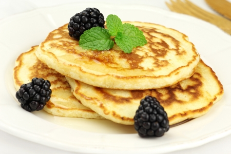 Delicious breakfast - fluffy pancakes topped with honey, blackberries and fresh mint