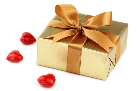 Valentine day gift wrapped with a golden paper and decorative satin ribbon bow with red hearts around on white background  photo
