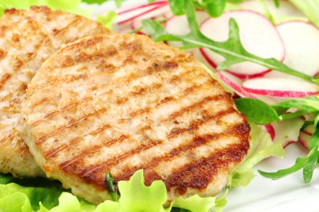 Delicious grilled rabbit burgers served with fresh salad and radish