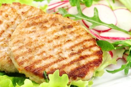 carne picada: Hamburguesas de conejo a la parrilla deliciosos servidos con ensalada fresca y rábano