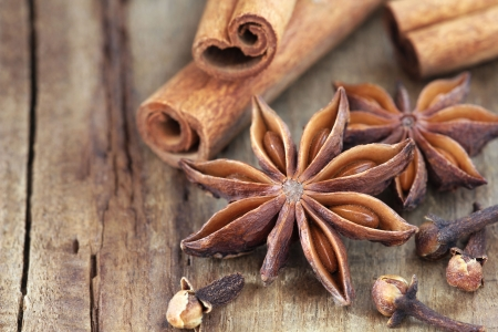 aniseed: Traditional Christmas spices - star anise, cloves and cinnamon bark sticks - on a rustic wooden table