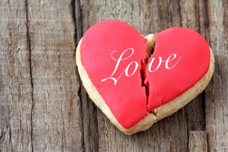 breakup: Cracked heart shaped cookie decorated with red icing as a concept of broken heart, breakup and end of relationship
