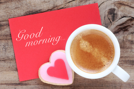 Cup of espresso with creamy foam with a romantic heart shaped cookie and a red greeting card with Good Morning message
