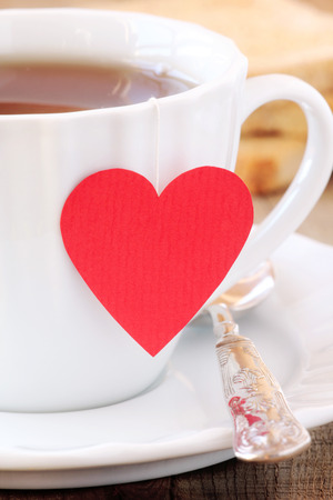good mood: Cup of tea with red heart teabag Stock Photo
