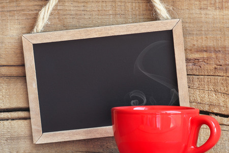 Framed vintage blackboard with a red cup of steamy coffee against wooden background with copy space