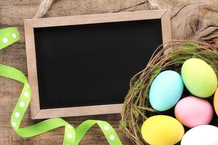 slateboard: Vintage blackboard on a wooden background with colourful Easter eggs