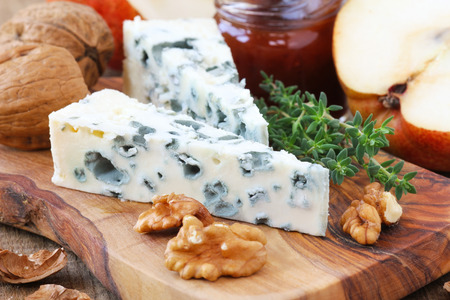 Slice of French Roquefort cheese accompanied with walnuts, pears and fresh thyme