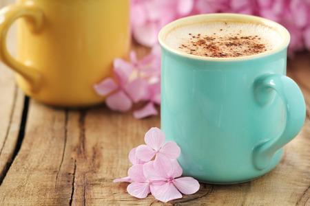Twee pastel kleur koppen cappuccino bestrooid met cacaopoeder en roze hortensia bloemen op een armoedige houten tafel Stockfoto
