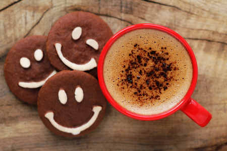 caffeine: Good morning or Have a nice day message concept - bright red cup of frothy coffee with smiling chocolate cookies